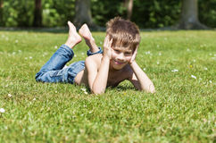 Blond pojke som ligger på gräs Arkivbilder