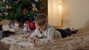 Blond pojke som ligger under julträdet och skrivar ett brev till jultomten arkivfilmer