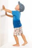 Blond pojke som skjuter honom väggvitbacground Royaltyfri Foto