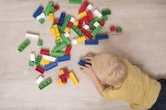 Blond pojke som spelar konstruktörn som ligger på golvet Top beskådar fotografering för bildbyråer