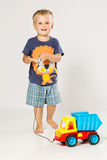 Blond pojke som spelar med den lilla plast- bilen Royaltyfri Fotografi