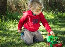 Blond pojke som spelar med lantgårdleksaken arkivfoto