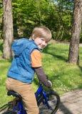 Blond pojke som tycker om cykelritt Royaltyfri Bild