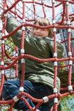 Blond pojke som tycker om den utomhus- lekplatsen Arkivfoto