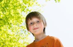 Blond pojke som tycker om solig dag i en parkera Arkivbild