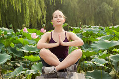 Blond pretty woman do yoga meditation exercise in the nature Stock Photo