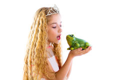 Blond princess girl kissing a frog green toad Stock Photos