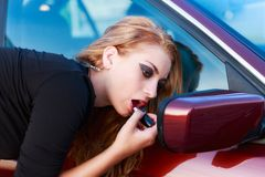 Blond putting lipstick on using the car mirror Royalty Free Stock Photo