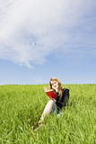Blond reading on grass Stock Photo