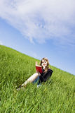 Blond reading on grass Royalty Free Stock Image