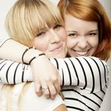 Blond and red haired girl friends laughing and hug. Red and blond haired girls friends laughing and hug Royalty Free Stock Photo