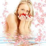 Blond with red and white rose petals and flowers i Stock Photography