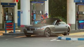 Blond in rich car, gas station service, fueling gasoline petrol. Stock footage stock video footage
