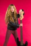 Blond rock and roll dziewczyna z basową gitarą na czerwieni Obraz Royalty Free