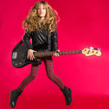 Blond Rock and roll girl with bass guitar jump on red stock photo