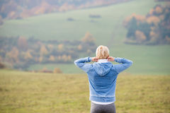 Blond runner outside in sunny nature, stretching. Rear view. Stock Image