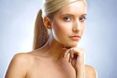 Blond's face and hand. Young lady's face and a hand. She is looking into the camera Stock Photo