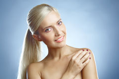 Blond's face and hand. Young lady's face and a hand. She is looking into the camera Royalty Free Stock Photo
