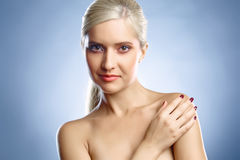 Blond's face and hand. Young lady's face and a hand. She is looking into the camera Royalty Free Stock Photos