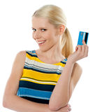 Blond salesgirl posing with credit card. And smiling at camera Royalty Free Stock Images