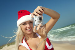 Blond in Santa Clause suit with camera Royalty Free Stock Photo
