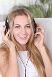 Blond schoonheidsmeisje dat hoofdtelefoons draagt Stock Foto's