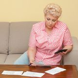Blond senior calculating her debts Stock Photo