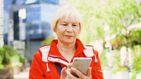 Senior woman standing outdoors using smartphone. Downtown business district on background. Blond senior woman in red coat standing outdoors using cellphone stock video