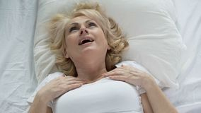 Blond senior woman waking up and touching her face, mask effect, skincare stock video footage