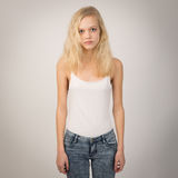 Blond Serious Girl Standing Straight Wearing A White Top. Studio portrait of a serious blond teenage girl with blue eyes and long hair wearing a white top Stock Photo