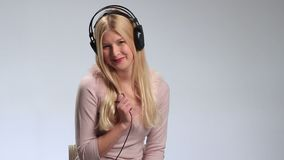 Blond sexig kvinna som poserar med hörlurar lager videofilmer