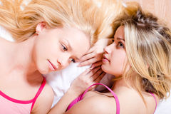 2 blond sexy attractive young green & blue eyes women, pretty sisters or girl friends relaxing in bed together closeup image Royalty Free Stock Image