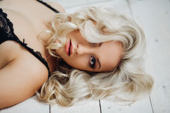 Blond sexy beautiful girl with luxurious long blond curly hair posing on a white background in black lingerie with lace Stock Photos