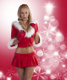 Blond sexy christmas lady. Sexy and beautiful blond young woman wearing a red christmas dress with hood and playing with dress fur Stock Photography