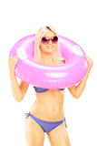 Blond sexy female in bikini holding a pink swimming ring Royalty Free Stock Images