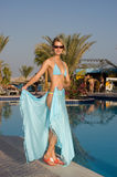 Blond sexy girl. Picture of a blond beautiful smiling girl wearing blue pareo and standing near pool Stock Images
