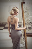 Blond sexy girl going up stair. Very cute woman , in evening dress going up stair in elegant indoor ambient, she has hair style . vintage color Royalty Free Stock Photography