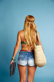 Blond sexy tourist girl short jeans and basket bag. Blond sexy tourist girl with short jeans and basket bag and flip flop shoes going beach Royalty Free Stock Photos