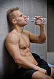Blond shirtless athlete drinking water after workout Stock Photography