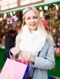 Blond shopping på julmarknaden Fotografering för Bildbyråer