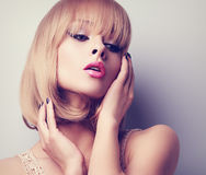 Blond short hair style woman with pink lipstick posing. Toned cl Royalty Free Stock Images