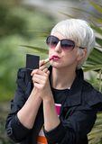 Blond Short Haired Woman Applying Pink Lipstick Outside Royalty Free Stock Images