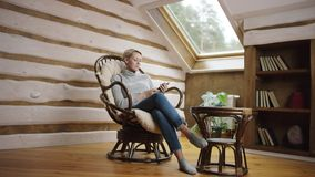 Blond woman surfing the Internet on smartphone sitting in a chair. Blond short haired woman surfing the Internet on smartphone sitting in a chair on the attic stock video