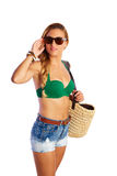 Blond short jeans sexy tourist woman going beach. With basket bag and sungrlasses on hair Stock Photography
