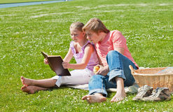 Blond siblings reading book. Teenager siblings reading book at picnic in the park in a bright sunny day Stock Image