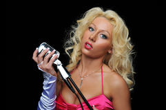 Blond singer on microphone. Blond singer on vintage microphone against a black background royalty free stock photography