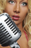 Blond singer on microphone royalty free stock photo