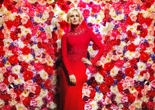Blond slim woman over the flower wall Royalty Free Stock Image