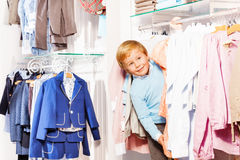 Blond small boy playa hide-and-seek in clothes Stock Image