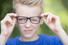 Blond smart teenager boy outdoor. Portrait smart looking blond teenager with glasses and a blink of an eye, thoughtful and clever, outdoor with green blurred royalty free stock image